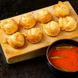 明石焼の出汁の常識を覆す、赤い出汁。ヤンニョンジャンとニラを使い、辛さの中に旨味が広がる新しい味わい